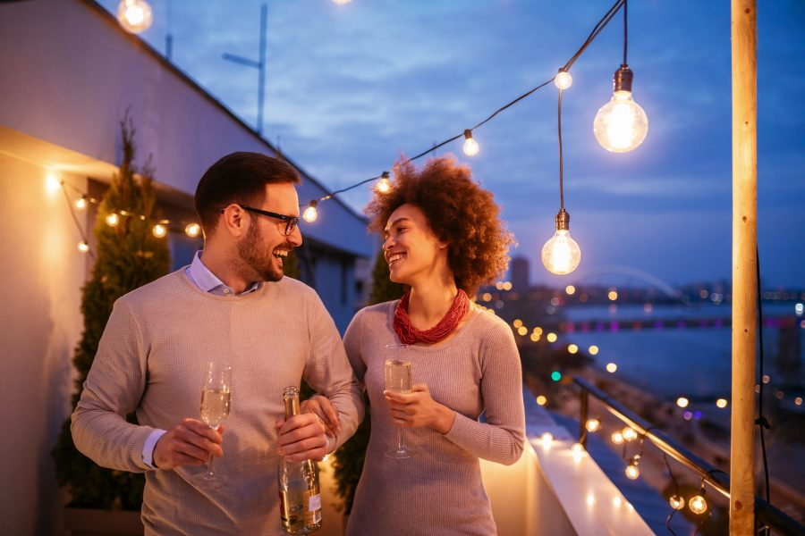 Couple holding champagne glasses at night on romantic Savannah getaway