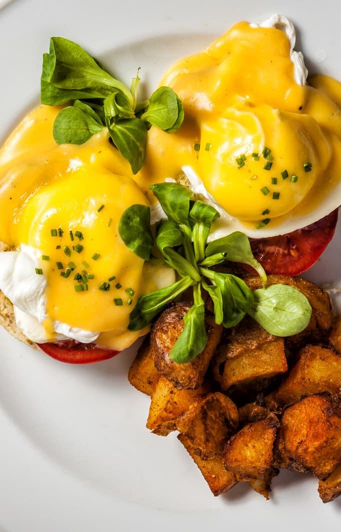 Eggs Benedict served with breakfast potatoes