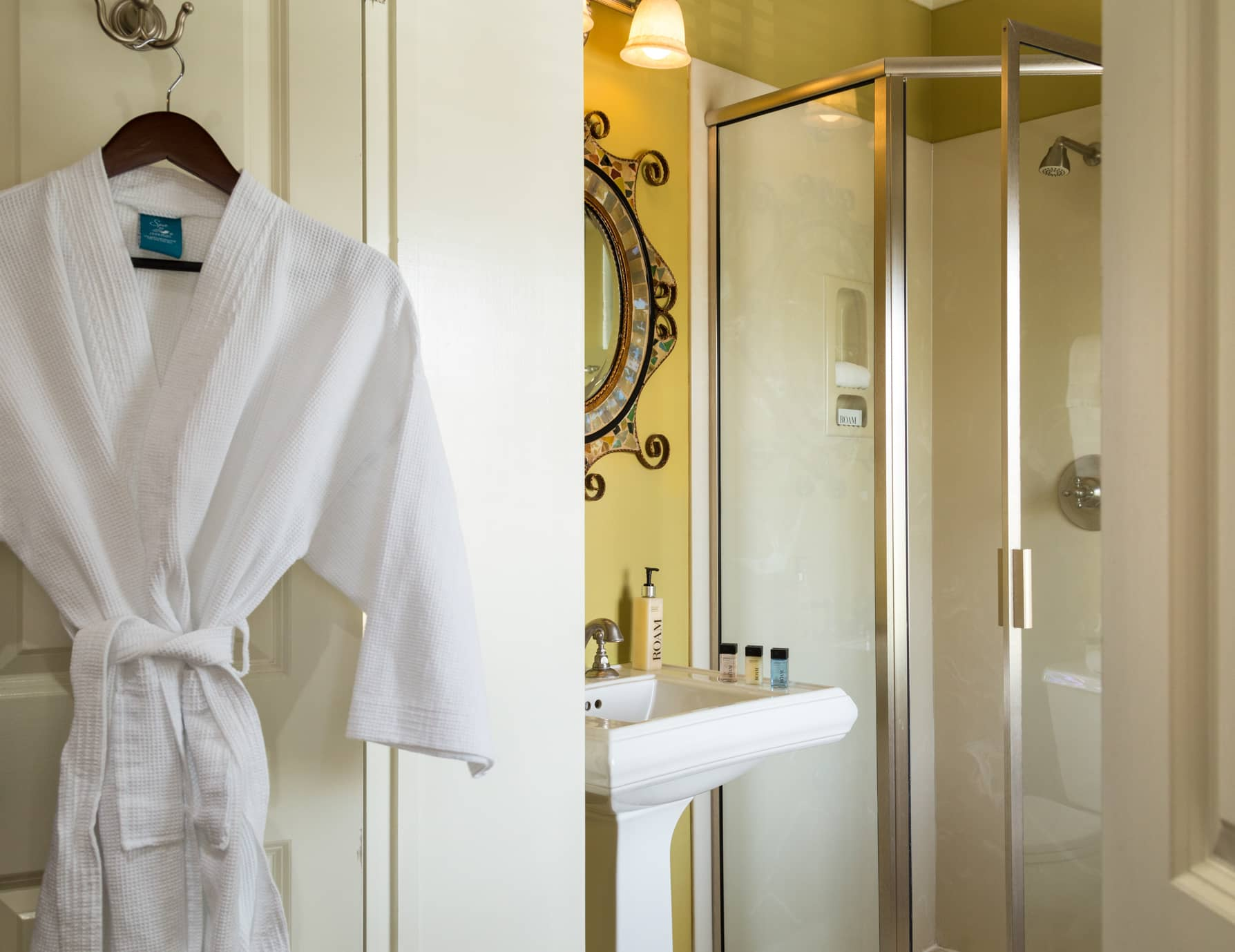 A bathroom with a walk-in shower and a white robe hanging on the bathroom door