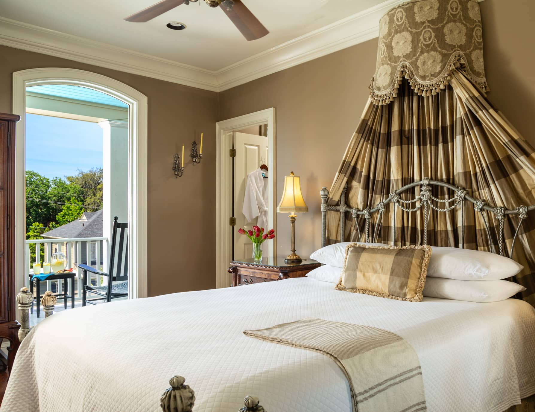 Queen bed in the Lafayette room with a ceiling fan and a door leading to a private balcony