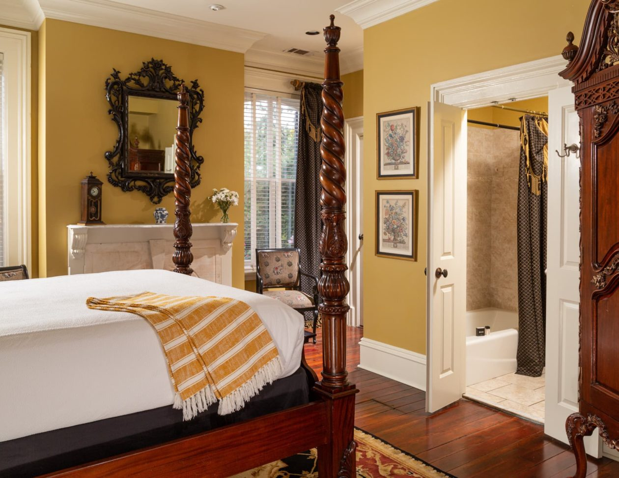 A queen bed in a room with ample light with a mahogany gilded Chippendale armoire