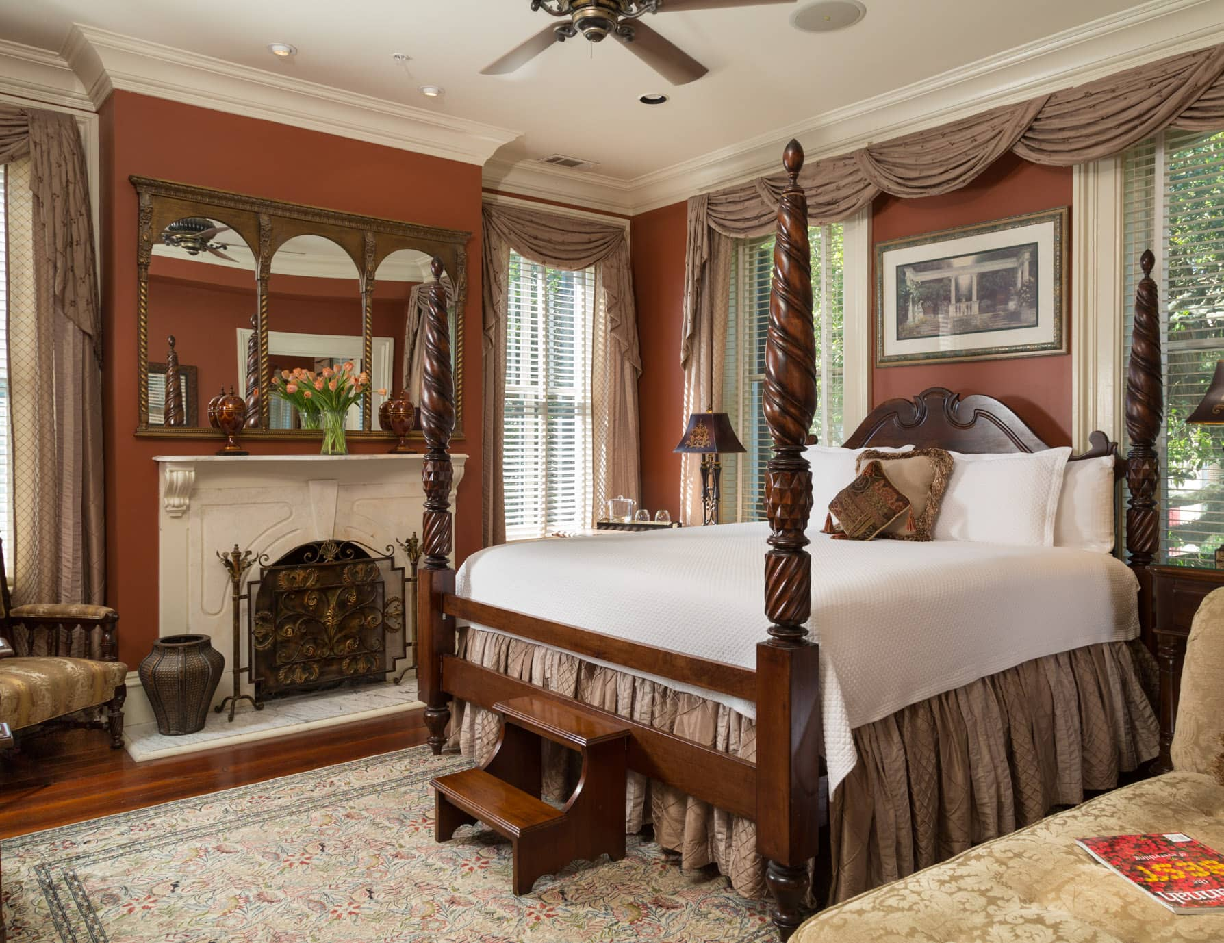 A large room with ornate furnishings a king bed, and fireplace with 4 large windows