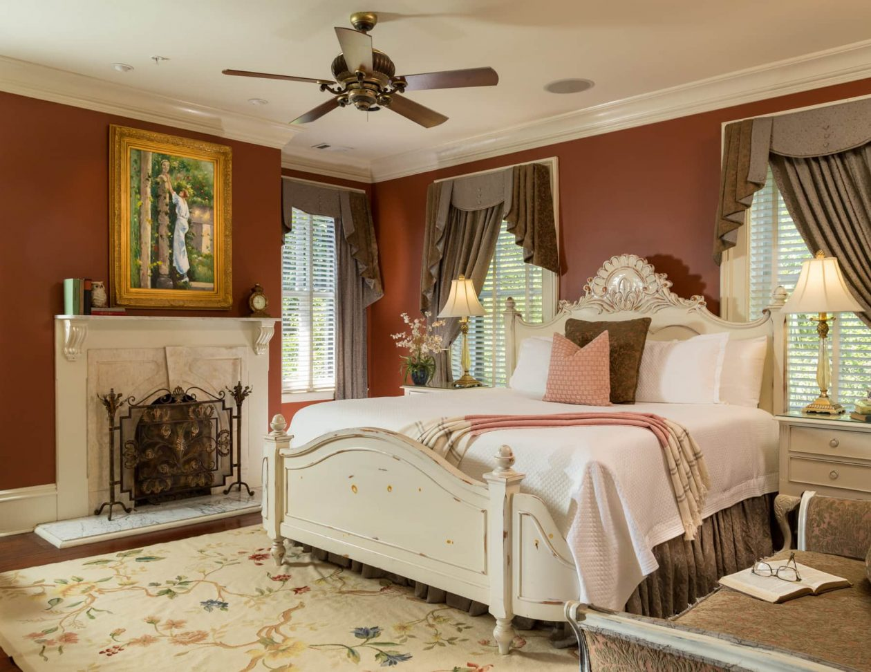 King bed in a room with a fireplace and a ceiling fan