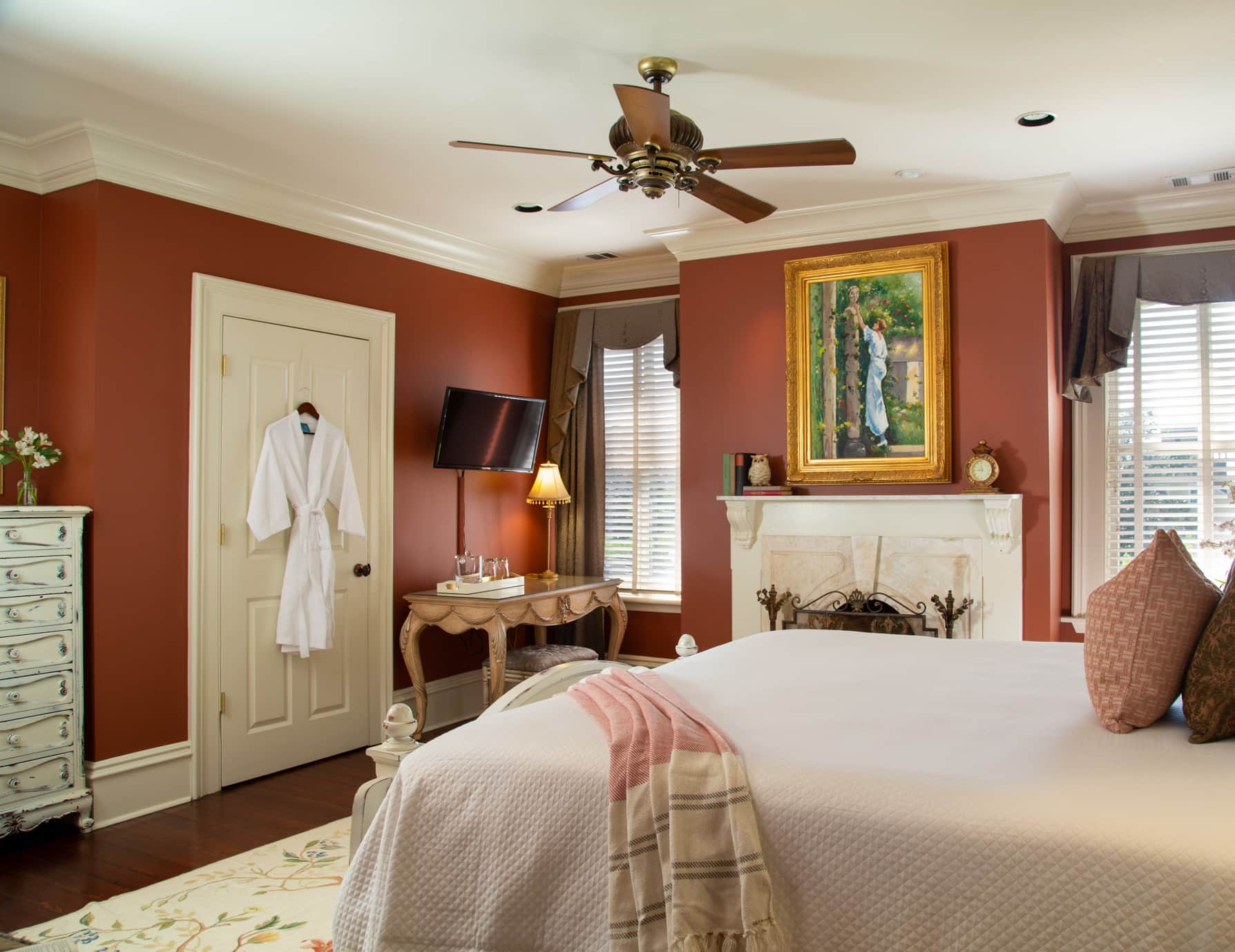 King bed in a room with a fireplace, ceiling fan, and large windows
