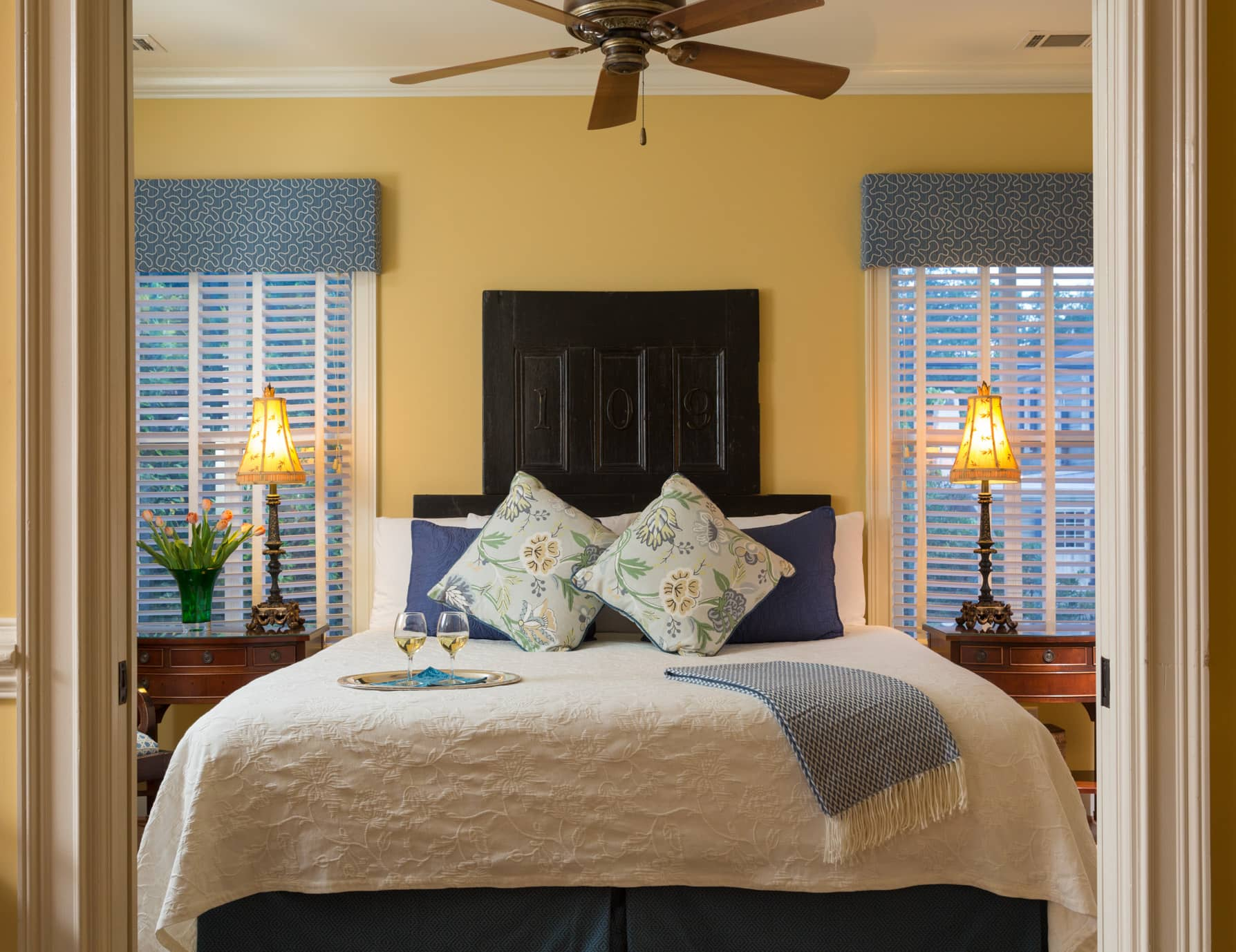King size bed in a bedroom with a ceiling fan and two end tables