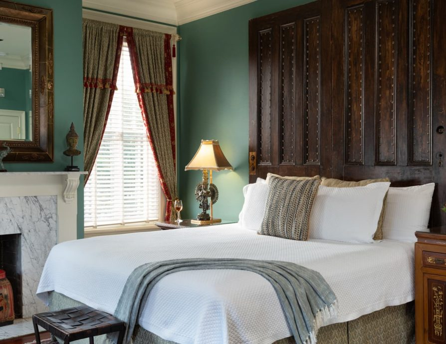 King bed in a room with a fireplace and hardwood floors