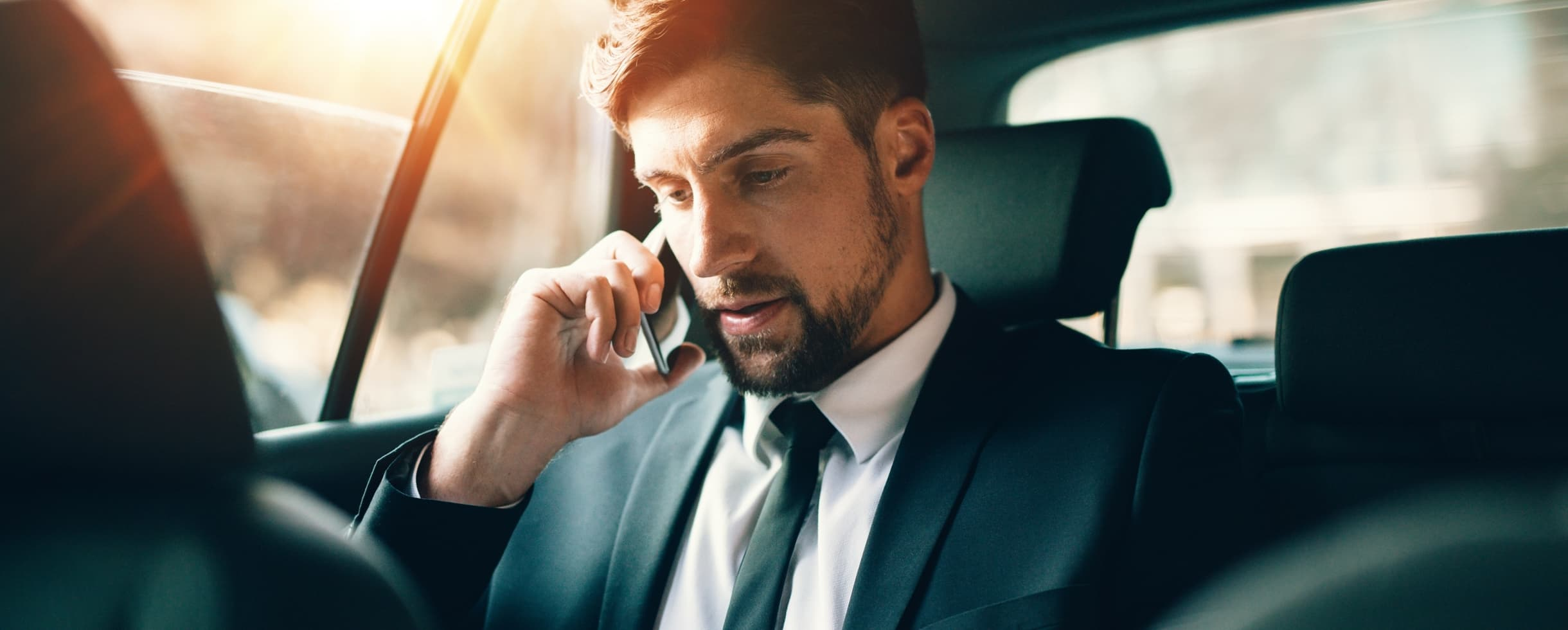 Business man in a suit on the phone in the back of a car