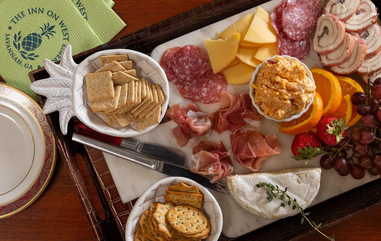 An assortment of cheeses, meats, fruit and crackers on a tray