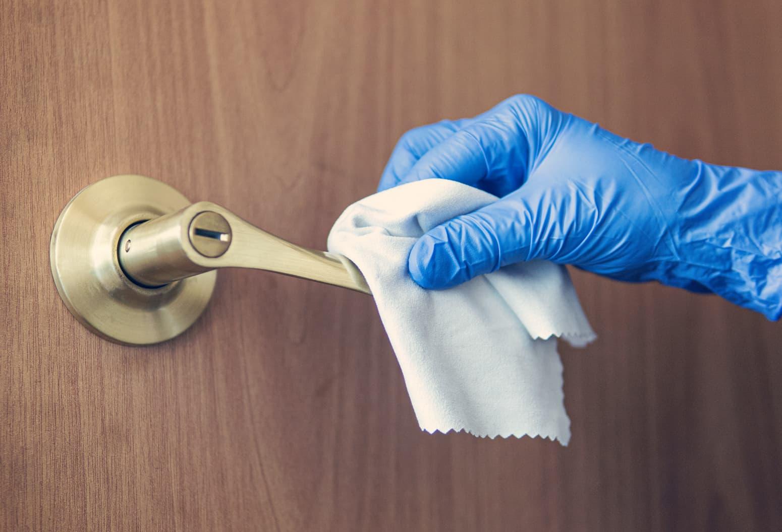 Person wearing gloves disinfecting a door handle