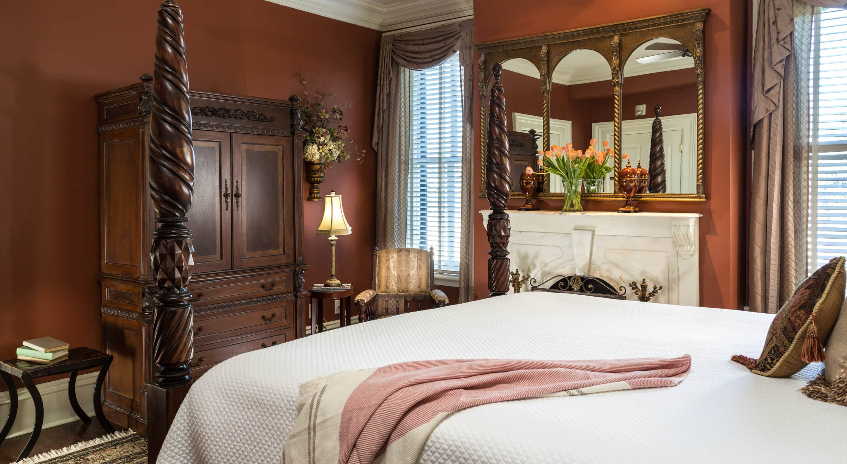 The end of a a four poster king bed with a fireplace and mirror