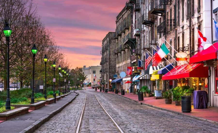 a street in Savannah with a trolley track and flags