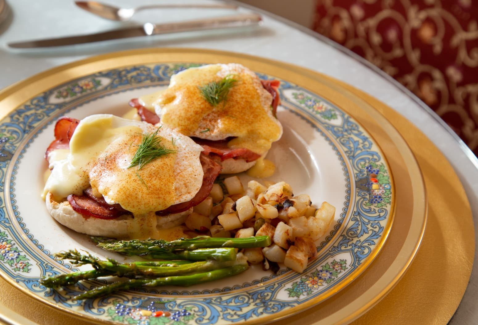 Eggs Benedict served with asparagus and breakfast potatoes