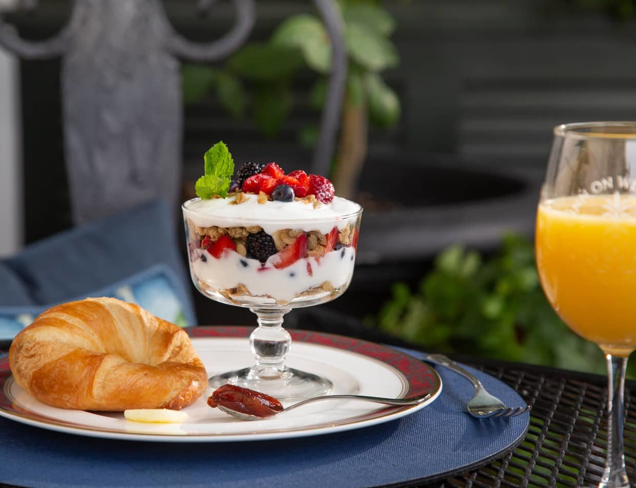A fruit parfait and a croissant served with orange juice on an outside patio table