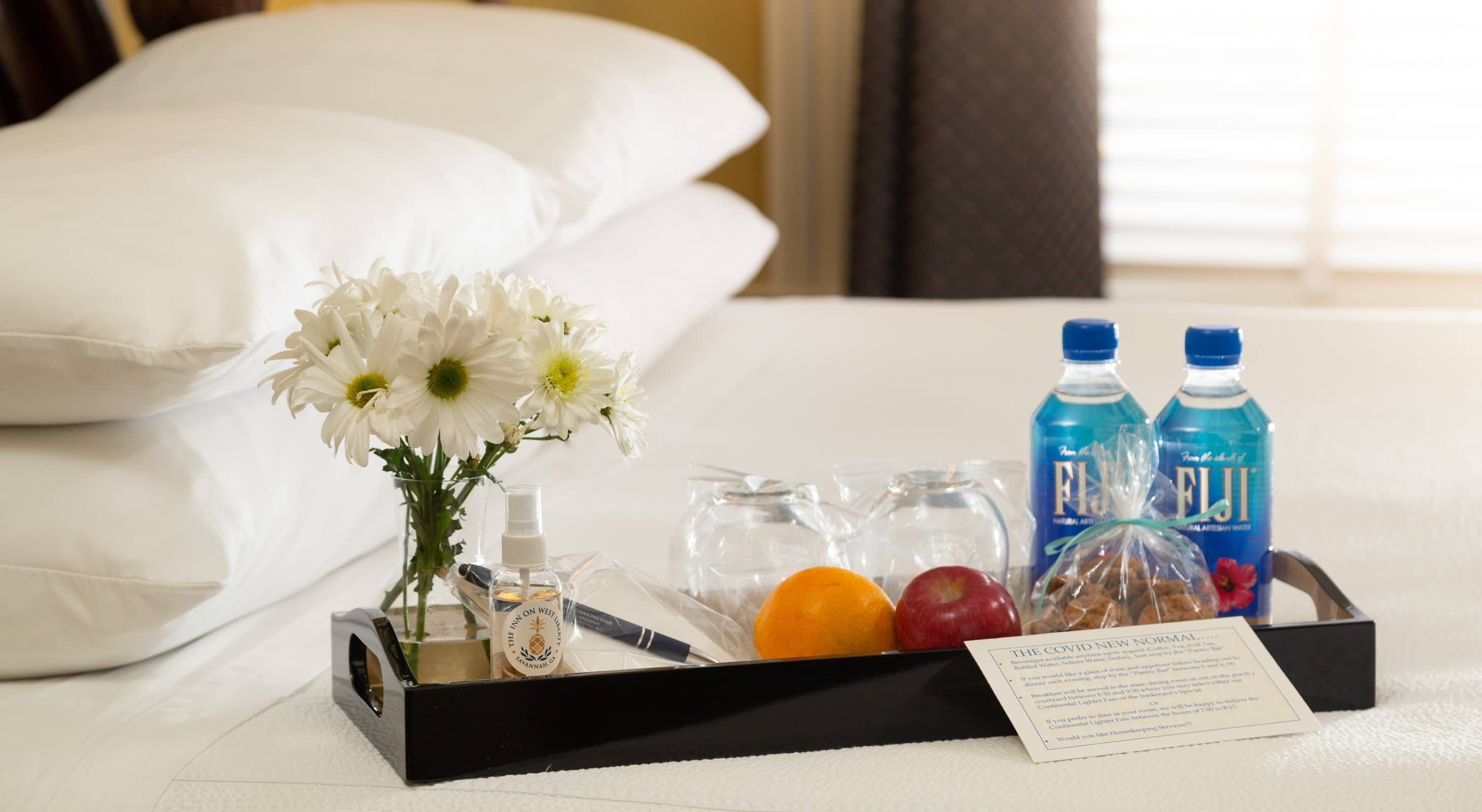 A refreshments tray with fruit, individually wrapped cookies, Fiji bottled water, hand sanitizer and flowers on a bed with white pillows and white linens