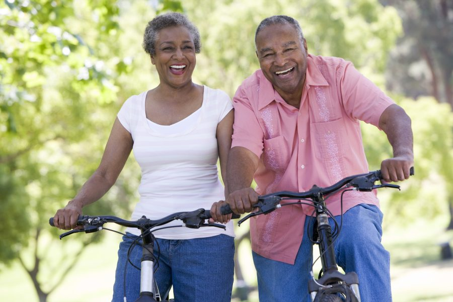 an older black couple riding bikes together