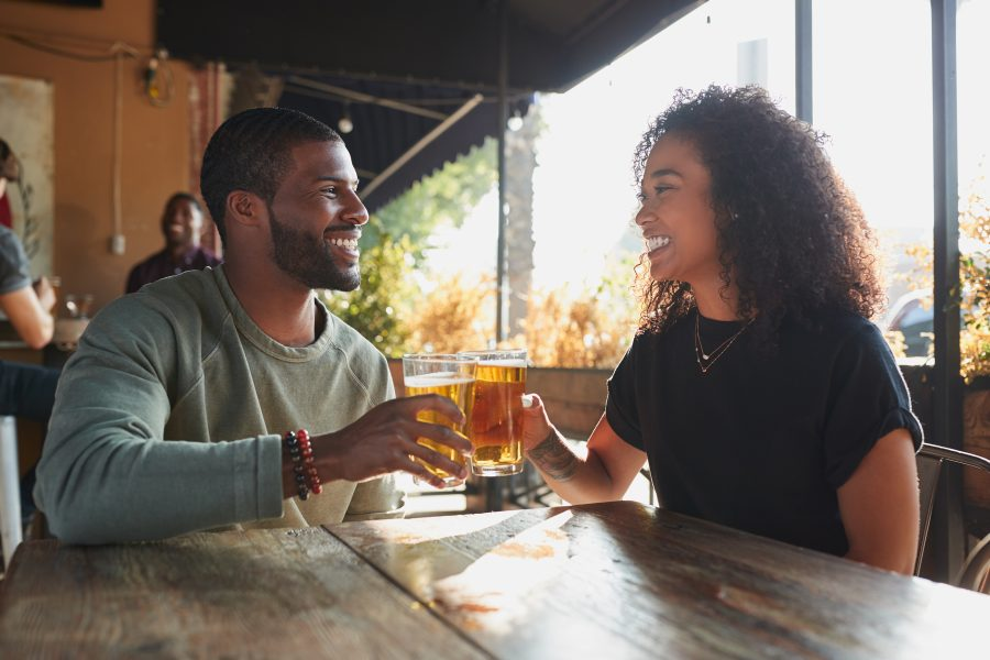 man and woman having beers at a bar