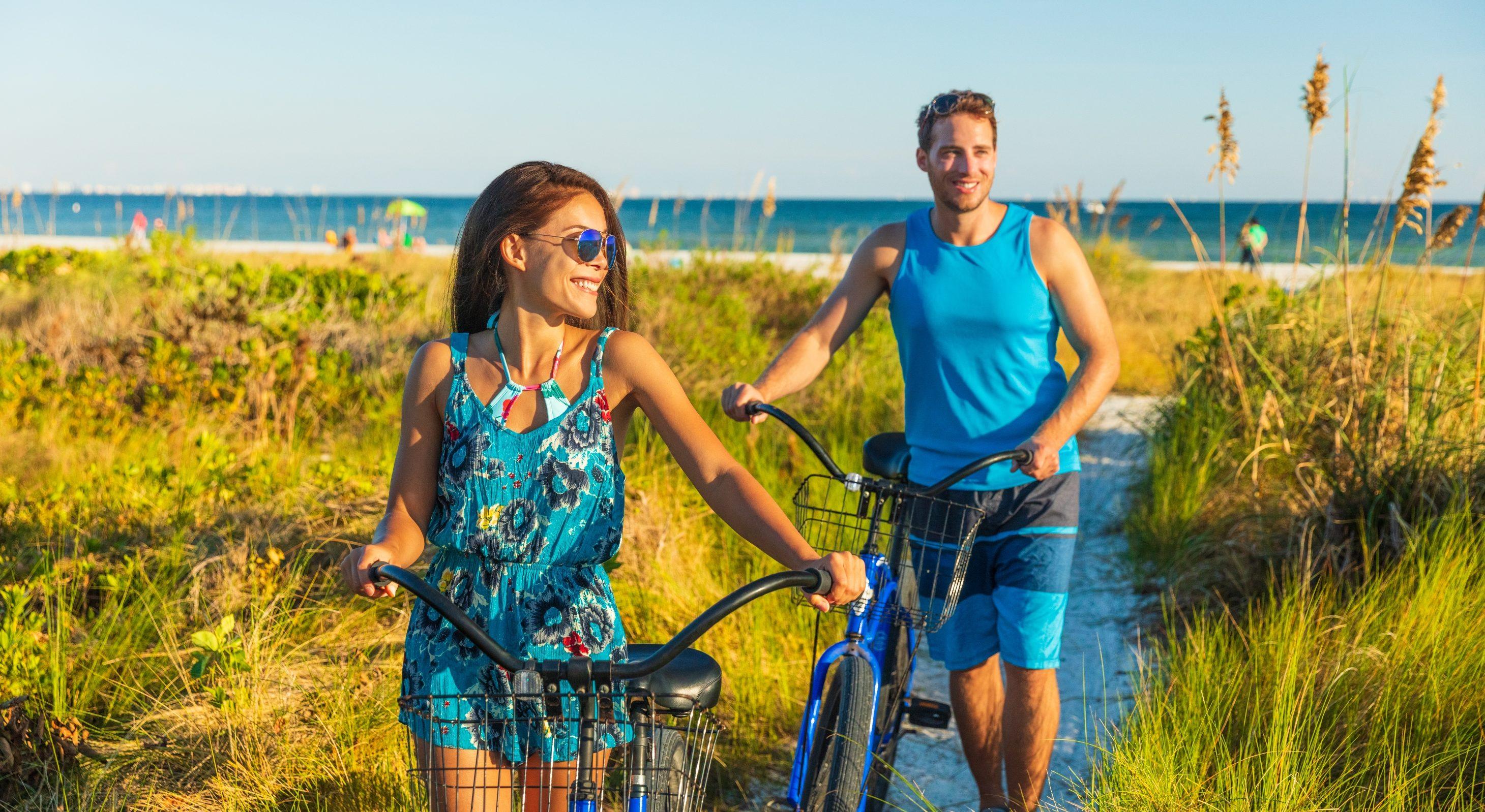 a couple biking on the beach