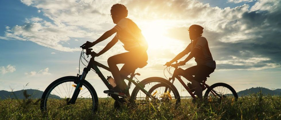 a couple riding bikes at sunset